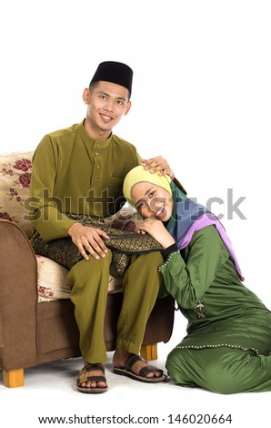 Husband and wife asking forgiveness during Eidul Fitri celebration. - stock photo