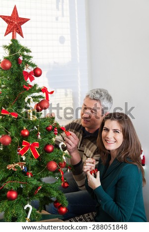 Husband and wife decorating christmas tree