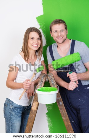 Husband and wife doing DIY renovations and redecorating their new home together painting it a bright green posing on a stepladder smiling at the camera - stock photo