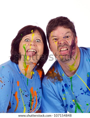 Husband and wife had a fun paint fight and now making faces at the camera.