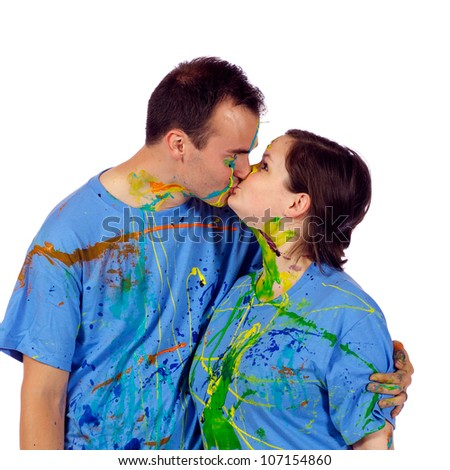 Husband and wife had a fun paint fight. Now they are kissing each other in front of the camera.