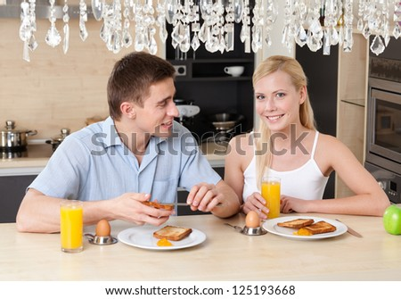 Husband and wife have breakfast in the modern comfortable kitchen