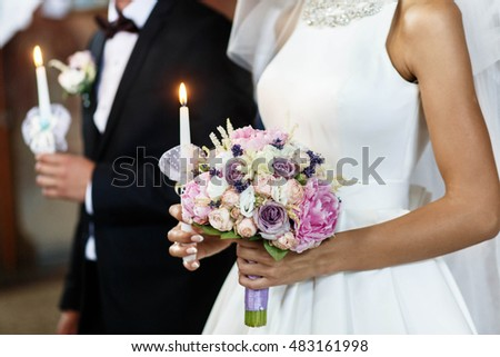 husband and wife hold candles on wedding ceremony