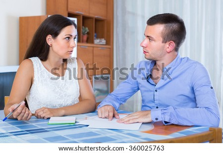 Husband and wife quarreling at banking statement indoors