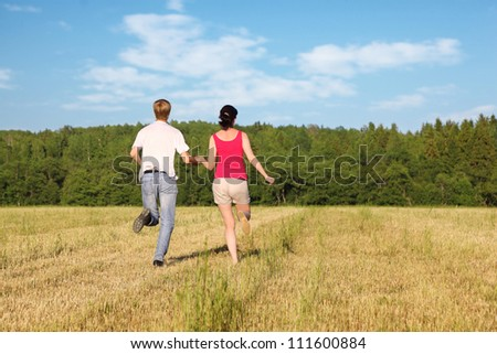 Husband and wife running in field - stock photo