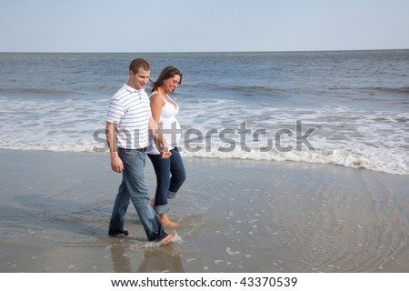 Husband and wife walk on beach holding hands