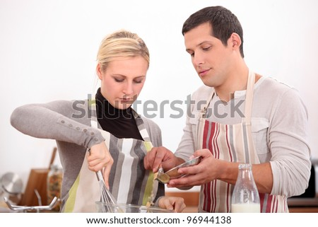 husband and wife whisking mixture - stock photo