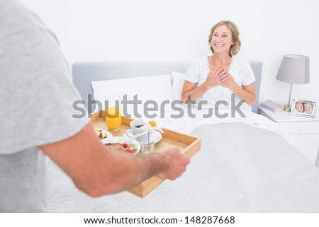 Husband bringing breakfast in bed to delighted wife in bedroom at home - stock photo