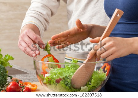 Husband disturbing his wife in making a salad