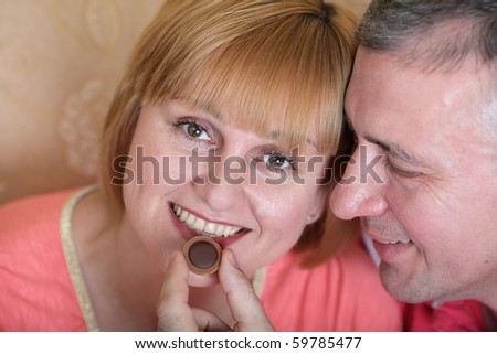Husband gives his wife a candy - stock photo