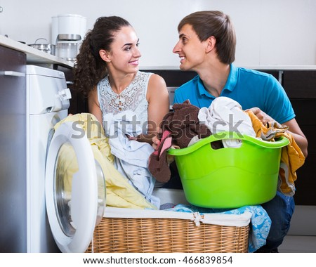 Husband helping happy european housewife to use washing machine indoors