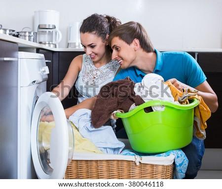 Husband helping happy spanish housewife to use washing machine indoors - stock photo