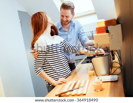Husband helping wife in kitchen prepare meals - stock photo