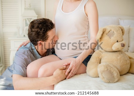 Husband kissed his pregnant wife belly - stock photo