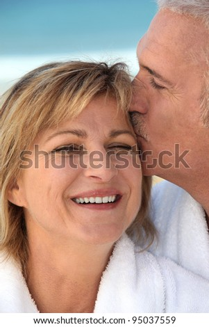 Husband kissing his wife - stock photo