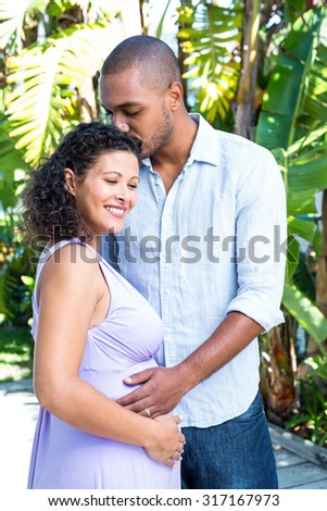 Husband kissing pregnant wife head in yard