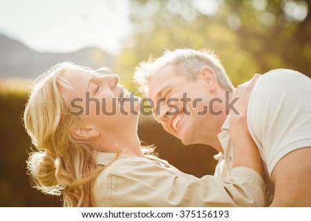 Husband kissing wife on the neck outside