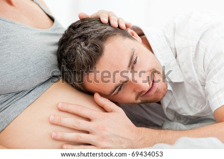 Husband listening to his wife's belly - stock photo