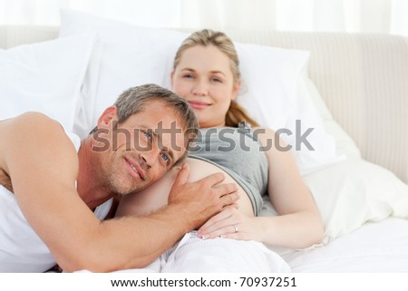 Husband listening to his wife's belly at home