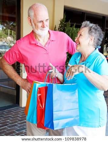 Husband looks disgusted with his wife who has spent too much money shopping. - stock photo