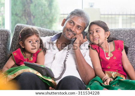 Husband making a phone call to wife while taking care of children at home. Asian Indian family at home. - stock photo