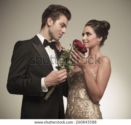 Husband offering his beautiful wife a bunch of red roses, they are looking at each other. - stock photo