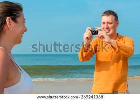 husband photographing his wife at the resort - stock photo