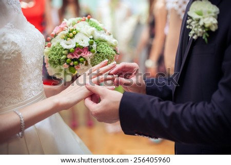 Husband puts a wedding ring on bride's finger. Bride with wedding bouquet. - stock photo
