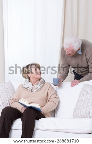 Husband serving his wife cup of coffee - stock photo