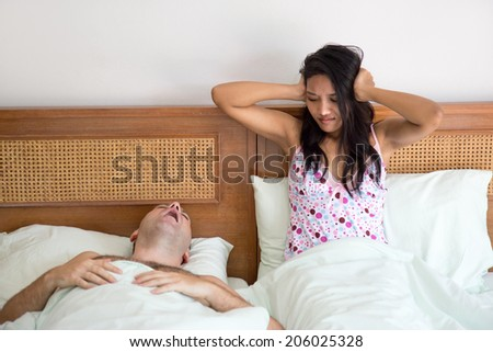 Husband snoring in sleep. Woman in bed blocking ears beside snoring man.Man snores in bed with unfortunate partner. Difficulty sleeping couple in bed. Strong hoarseness sleeping man wakes up his wife. - stock photo