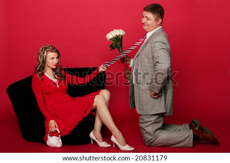 Husband standing on his knee in front of wife with bouquet of roses and ask pardon