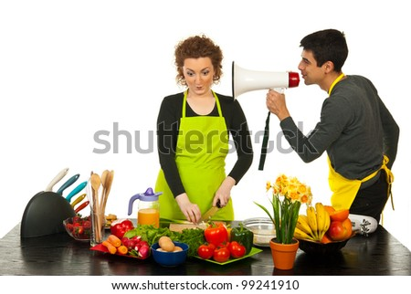 Husband telling by megapone to his wife to cook faster against white background - stock photo