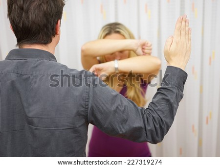 Husband wants to  harm his wife with slap, domestic violence - stock photo
