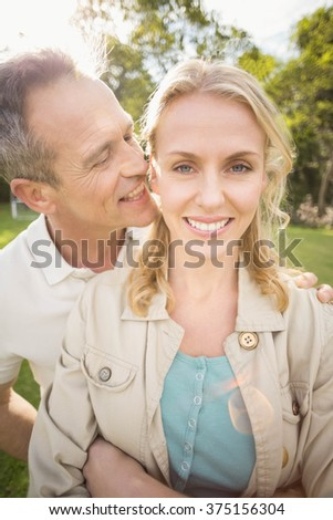 Husband whispering something to wife's ears outside - stock photo
