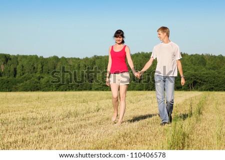 Husband, wife holding hands walk in field near wood - stock photo