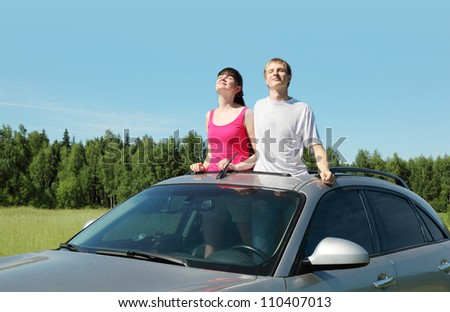Husband, wife stand in hatch of car in field
