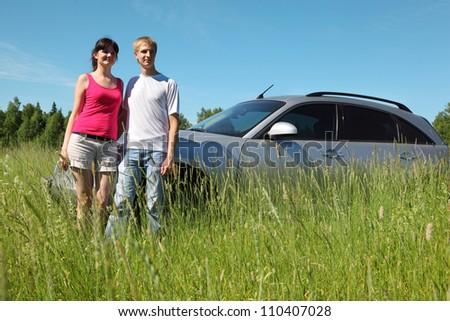 Husband, wife stand near car in field - stock photo