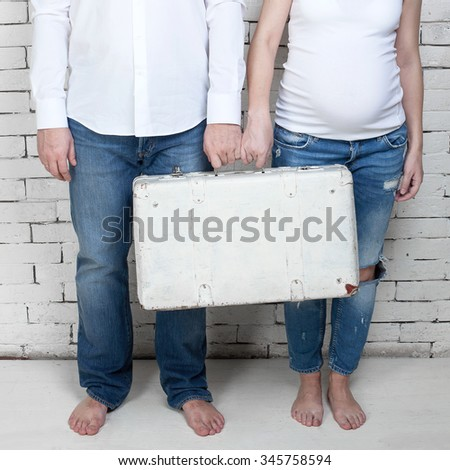 Husband with pregnant wife holding the white suitcase against a white wall - stock photo