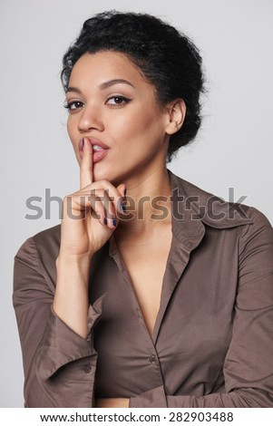 Hush. Portrait of mixed race caucasian - african american business woman with finger on her lips - stock photo