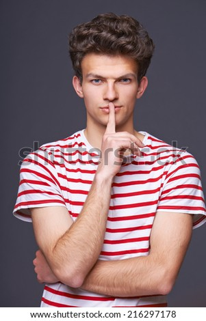 Hush. Young serious sullen man silencing you, with finger on lips over gray background - stock photo
