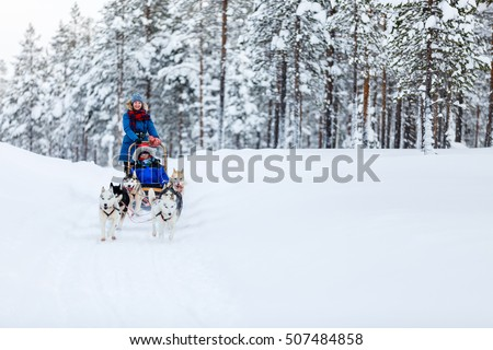Husky dogs are pulling sledge with family at winter forest in Lapland Finland
