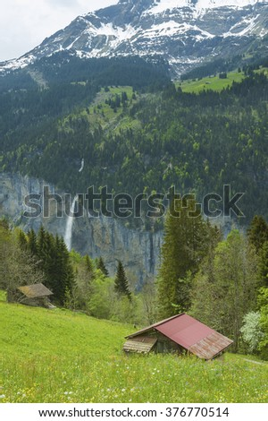 Hut and waterfall in Lauterbrunnen, Switzerland - stock photo
