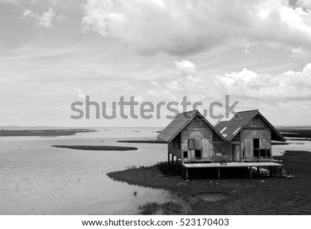 hut in a field that was flooded is black and white photo