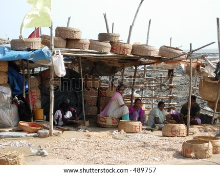 hut of poor people surrounded by baskets - stock photo
