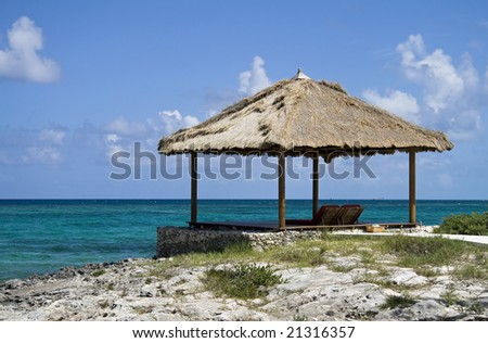 Hut on the edge of beautiful tropical beach. - stock photo