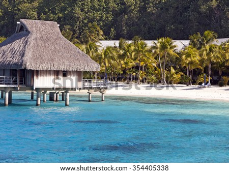 Hut over the transparent quiet sea water  and a palm tree - stock photo