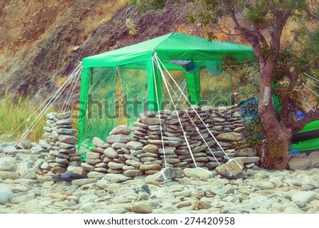 Hut with sun awning made with his own hands on the beach with rocks - stock photo