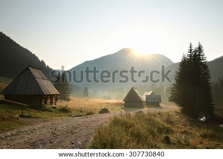 Huts along the trail in a valley surrounded by mountains, the Carpathians. - stock photo