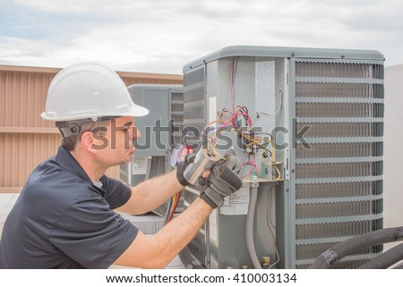 HVAC technician working on a capacitor part for condensing unit.  - stock photo