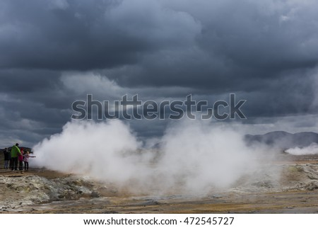 Hverarond, Iceland - June 30, 2016: Steam pits of Geothermal landscape Hverarond on Iceland with red dirt, a hot water stream and lots of steam.